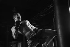 The fighter of mixed martial arts with a shout is hitting the ba. G with a knee Royalty Free Stock Images