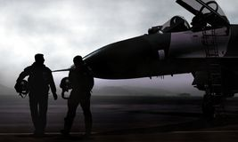 Fighter pilot and jet on military airbase at dawn. Fighter pilot with supersonic jet on military airbase at dawn Stock Images