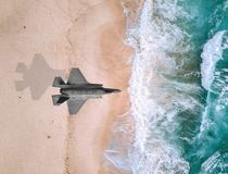 Fighter plane flies over a sea. F35 flying over sea. The Lockheed Martin F-35 Lightning II is a family of single-seat, single-engine, all-weather, stealth stock image