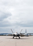 Fighter Plane Ready to Take Off. A military plane on a runway against a cloudy sky. Front view. The file contains an embedded clipping path Stock Photo