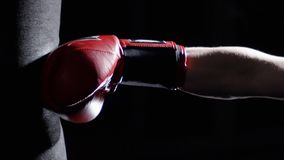 Fighter Practicing Some Kicks With Punching Bag - A Man With A Tattoo Boxing On dark Background. Kick, punching bag on stock image