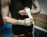 Fighter preparing for training, wrapping hands with boxing wraps Stock Photos