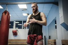 Fighter preparing for training, wrapping hands with boxing wraps Stock Image
