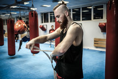 Fighter preparing for training, wrapping hands with boxing wraps Stock Images