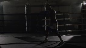Fighter shadowboxing on training ring. Professional fighter. Male boxer in training sportswear, an exercise in sports. Hall, fight with a shadow in ring, Strike stock video footage