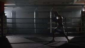 Fighter shadowboxing on training ring. Professional fighter. Male boxer in training sportswear, an exercise in sports. Hall, fight with a shadow in ring, Strike stock video