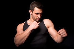 Fighter silhouette. Handsome athletic man in boxing stand on a dark background. Stock Photography