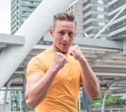 Fighter sport fitness. Handsome athletic man in boxing stand in modern city. Fighter sport fitness athletic man in boxing stand in modern city stock image
