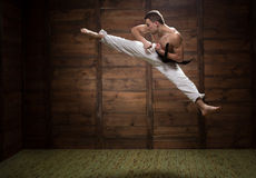 Fighter. He strong and jumpy. Fighter jumping with foot kick in dojo Royalty Free Stock Photo