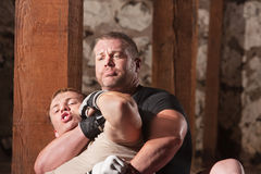 Fighter Struggling in Choke Hold. Blond mixed martial arts fighter being choked from behind Stock Photo