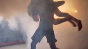 A lean fighter throws his enemy to the floor. A fighter throws his enemy to the floor in the deeply fogged cage stock footage