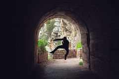 Fighter training in a dark tunnel. Silhouette of a man jumping while practicing karate in a dark tunnel stock image