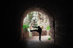 Fighter training in a dark tunnel. Silhouette of a man practicing karate moves and techniques in a dark tunnel royalty free stock photos