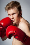 Fighting blond man with boxing glove Royalty Free Stock Image