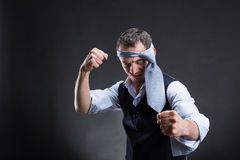 Fighting businessman with a tie on his head Royalty Free Stock Images