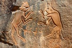 'The Fighting Cats' Engraving - Wadi Mathendous. Iconic Engraving of 'The Fighting Cats' (Meercatze) at Wadi Mathendous Archeological Site, Sahara, Libya Royalty Free Stock Images