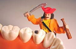 Fighting cavities concept #2. A pirate with a sword is fighting cavities and proving that everyone should brush their teeth to prevent caries. A miniature figure stock photo