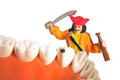 Fighting cavities concept. A pirate with a sword is fighting cavities and proving that everyone should brush their teeth to prevent caries. A miniature figure is Royalty Free Stock Photo