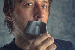 Fighting censorship, man removing duct tape from mouth. Fighting censorship, adult caucasian man removing duct tape from mouth that prevented him from speaking royalty free stock photo