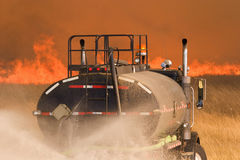 Fighting fire. A water truck helps to fight a large grass fire royalty free stock image