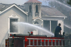 Fighting a Fire. Firefighters spray water on a burning home Stock Photography