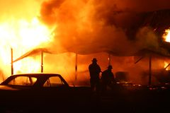 Fighting fire. Two fire fighters fighting a structure fire royalty free stock photography