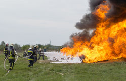 Fighting fire with a foam extinguisher. Szeged, Algyo, Hungary - October 8, 2015: Regional fire-fighting exercise in the training area with urban and contract Stock Photo