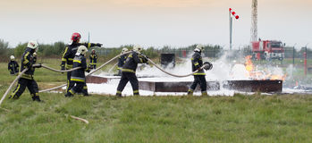 Fighting fire with a foam extinguisher. Szeged, Algyo, Hungary - October 8, 2015: Regional fire-fighting exercise in the training area with urban and contract Stock Photos