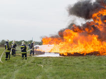 Fighting fire with a foam extinguisher. Szeged, Algyo, Hungary - October 8, 2015: Regional fire-fighting exercise in the training area with urban and contract Royalty Free Stock Photo