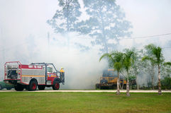Fighting Fire With Machines. Firefighters and equipment on the front lawn of a home fighting a brush fire encroaching on the property. Image shows a brush truck Royalty Free Stock Photos