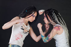 Fighting girls. White fighting girls with dreads on black background. One girl with body art on her hand Royalty Free Stock Image