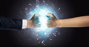 Fighting hands breaking glass. Two hands fighting and breaking glass into small pieces with blue light conceptn royalty free stock photos