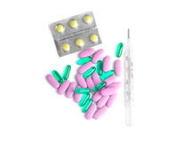 Fighting illness. Variety of pills to fight illness with thermometer on white Stock Image