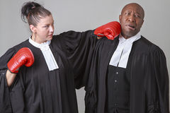 Fighting lawyer. Caucasian women wearing a lawyer toga punching a black men wearing a lawyer toga Stock Image