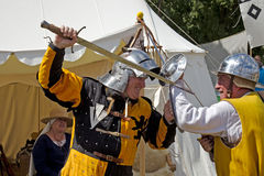Fighting men at arms. POTTEN END, UK - JULY 27: Two medieval man at arms reenactors play out a possible scene from a medieval combat using period weapons and Stock Photos