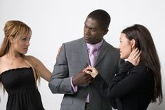 Fighting over a man. A young man stands between two young woman, his attention seemingly being wanted by both women. Jealousy, fighting over a man concepts Stock Images