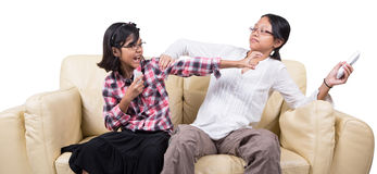 Fighting Over Remote Control. Sisters fighting over remote controls on a sofa royalty free stock image