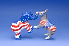 Fighting party mascots. Republican elephant and Democratic donkey fighting it out on a blue background Royalty Free Stock Photos