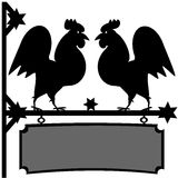 Fighting roosters sign. Two black rooster silhouettes that stand on top of a sign that can be hung on a wall Royalty Free Stock Image