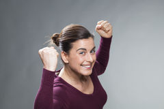 Fighting 30s woman glowing from within with hands up Stock Images
