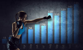 Fighting for sales dynamics . Mixed media. Boxer woman over dark background with graphs and diagrams Stock Photos