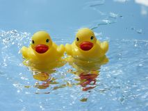Fighting the Tidal Wave. Two baby rubber duckies jumping the waves Stock Photography