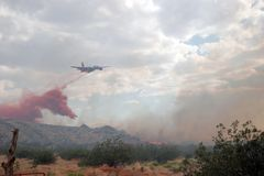 Fighting a wildfire. Aircraft dropping flame retardant on a wildfire royalty free stock photos