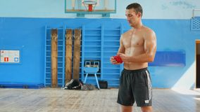 Fights without rules-mixed martial arts training. Athlete mixed martial arts after training shoot sports red bandages and throws them on the wooden floor stock video