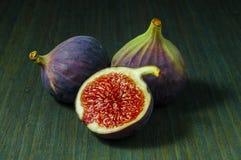 Figi, cały i przyrodni na zielonym drewnianym tle zdjęcia royalty free