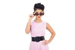 Figlarnie czarni włosy model patrzeje nad jej okularami przeciwsłonecznymi Fotografia Stock