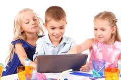 Figlarnie dzieci siedzi z laptopem obrazy stock