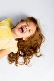 Figlarnie mała dziewczynka w kolor żółty sukni śmiać się Zdjęcia Stock