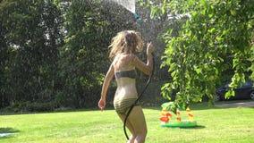 Figlarnie mokra kobiety dziewczyna odświeża pod wodą od węża elastycznego w ogródzie na gorącym letnim dniu 4K zbiory wideo