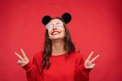 Figlarnie nastoletnia dziewczyna w mysz ucho pokazuje dwa palca zdjęcia royalty free